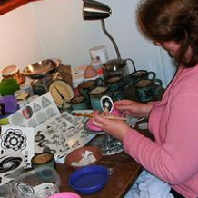 Diana putting decals on pots, graphic design fun